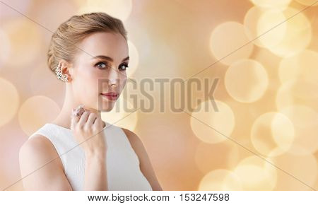 jewelry, luxury, wedding and people concept - smiling woman in white dress with diamond earring and ring over holidays lights background