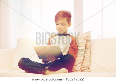leisure, children, technology and people concept - boy with tablet pc computer at home