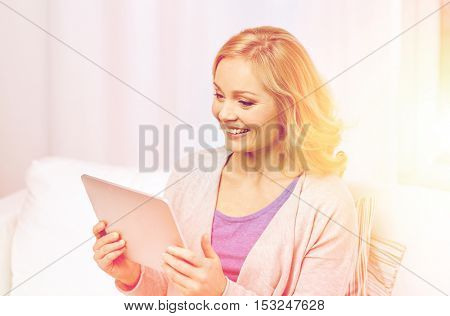 people, technology and internet concept - happy middle aged woman with tablet pc computer at home