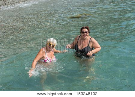 Two Women Are Standing In Clear Water Of Sea Shallow.
