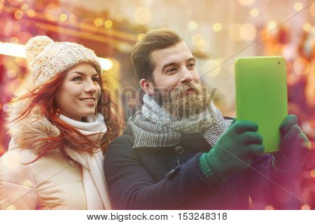 holidays, winter, christmas, technology and people concept - happy couple of tourists in warm clothes taking selfie with tablet pc computer walking in old town