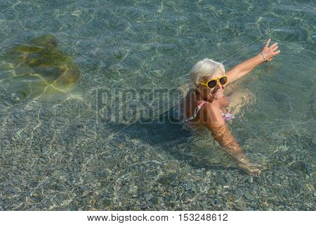 Aged Lady Is Sitting In Clear Transparent Water Sea Beach.
