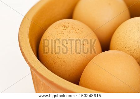 large earthenware bowl with fresh hens eggs isolated on white