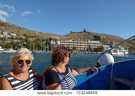 Two Women Are On Motor Boat In Balaklava Bay, Crimea.