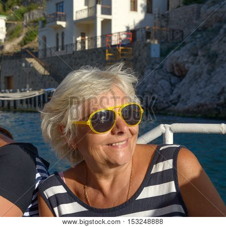 Close-up head and shoulders portrait of nice smiling senior blonde woman in summer afternoon sunlight.