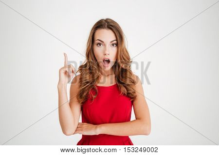 Portrait of a shocked brunette woman in red dress pointing finger up over white background