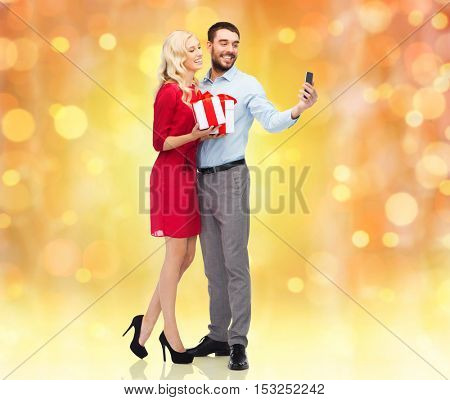people, christmas, couple, technology and holidays concept - happy young woman and man with birthday presents taking selfie by smartphone over lights background