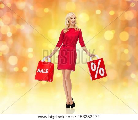 people, christmas, sale, discount and holidays concept - smiling woman in red dress with shopping bags over lights background