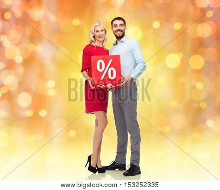 people, christmas, sale, discount and holidays concept - happy couple with red sale sign over lights background