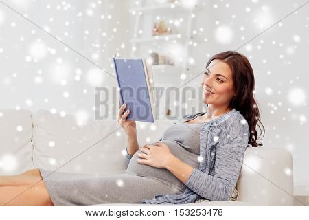 pregnancy, winter, christmas and motherhood concept - smiling pregnant woman lying on sofa and reading book over snow