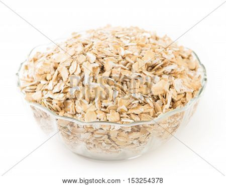 Oat flakes in a glass bowl isolated on white background.