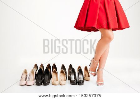 Cropped image of a woman in red dress standing near pairs of shoes over white background