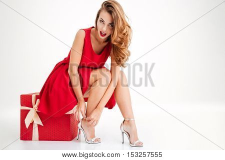 Excited young brunette woman in red dress trying on her new sandals while sitting on big gift box isolated on a white background