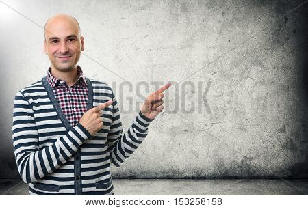 Man Pointing Finger At Copy Space Over Concrete Wall