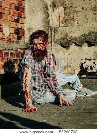 Zombie Man Sits On Asphalt