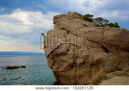 Massive rock formation stone or cliff with pine trees on top at sea shore coast beach over cloudy sky