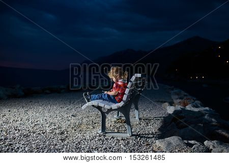 cute baby boy child with mobile phone on bench outdoor over dark twilight sky with clouds on beach with sea or ocean water on evening natural background