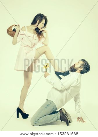 young couple of pretty girl with long hair and sexy body holding basket with fruits and handsome bearded man with beard holding flower bouquet sitting on knees makes proposal isolated on white