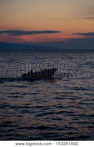 Motor boat floats in blue sea water along mountain coast after sunset over evening sky