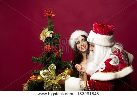 Happy santa claus man and pretty girl in new year red suit decorate Christmas tree