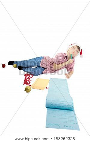 Boy writing a very long letter to Santa. Isolated on white background. Vertical orientation.