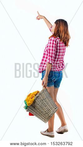 Back view of pointing woman with  basket of dirty laundry. girl is engaged in washing. Rear view people collection.  Isolated over white background. Girl in shorts and shirt shows a hand up