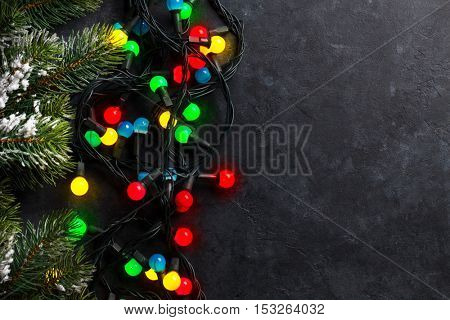 Christmas stone background with snow fir tree and colorful lights. Top view with copy space