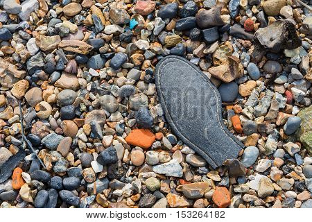 Discarded remains of a shoe on a pebble beach