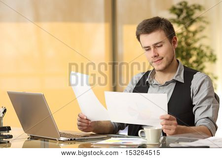 Attentive businessman working comparing paper documents sitting in a desk at office