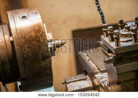 Color image of an old lathe in a workshop.