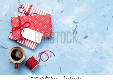 Christmas background with gift boxes and coffee cup on stone table. Top view with copy space. Gift wrapping