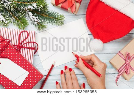 Female writing christmas greeting card and gift wrapping. Top view with copy space