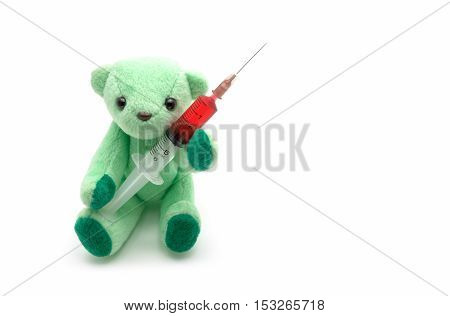 Small green teddy bear holding red injection syringe on white background children medical concept