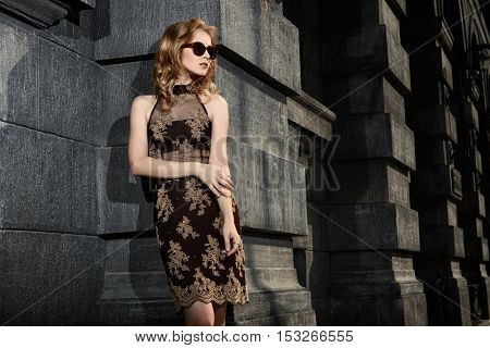 Beautiful fashion woman standing on a city street. Vogue shot.