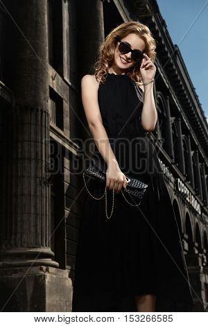 Beautiful smiling blonde woman in long black dress and sunglasses in the city center. Fashion model outdoor.