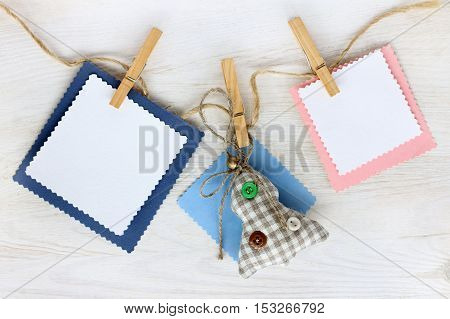 Christmas tree and blank cards for lettering hanging from a rope on the background of whitewashed wood / garland for holiday decorations