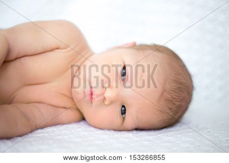 Close-up portrait of sweet newborn infant lying quietly on white bed serious looking away