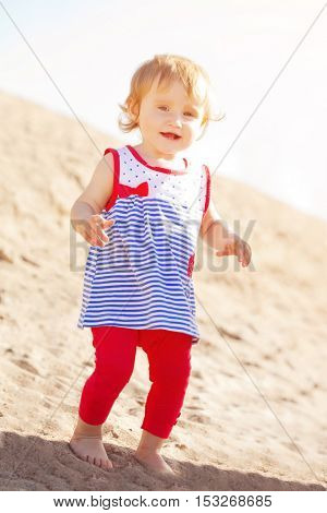 Cute little smiling baby girl on the beach