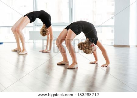 Graceful little girl ballerina and her teacher stretching and exercising in ballet studio