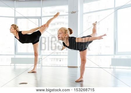 Beautiful young woman and little girl ballerina dancing in ballet school