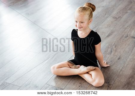 Portrait of cheerful cute little girl ballerina sitting with legs crossed in ballet studio