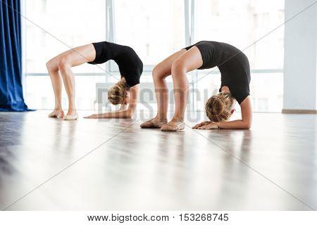 Flexible little girl ballerina and her teacher exercising in dance studio