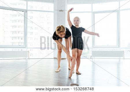 Graceful little girl ballerina and her teacher training and dancing in ballet school