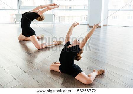 Graceful little girl ballerina dancing together with her teacher in ballet school