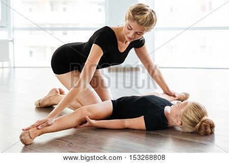 Beautiful young woman teaching and stretching little girl ballerina in ballet class