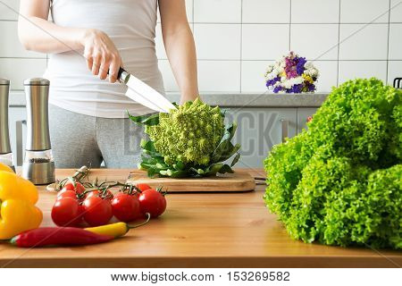 Young Woman Cooking Romanesco Broccoli In The Kitchen