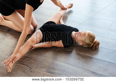 Little girl lying on the floor and doing stretching exercises with her teacher at studio