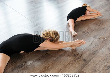 Young attractive ballet teacher and her little student doing stretching exercises on the floor at studio
