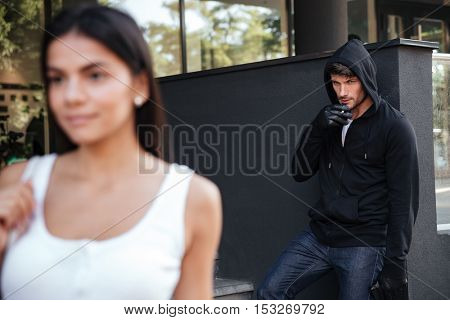 Dangerous man robber smoking and looking at young woman walking in the city