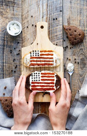 sandwich with image of american flag in womans hands on wooden table. Top view.